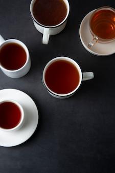 Widok z góry wielu filiżanek, kubków z gorącą herbatą pić w ciemności