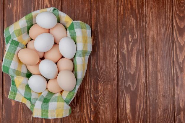 Widok z góry wielu świeżych jaj kurzych na sprawdzonym obrusie na drewnianym tle z miejsca na kopię