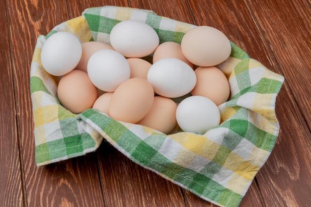 Widok z góry wielu świeżych jaj kurzych na żółtym i zielonym obrusie sprawdzone na drewnianym tle