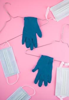 Widok z góry wieszaków drucianych z rękawiczkami chirurgicznymi i maskami medycznymi