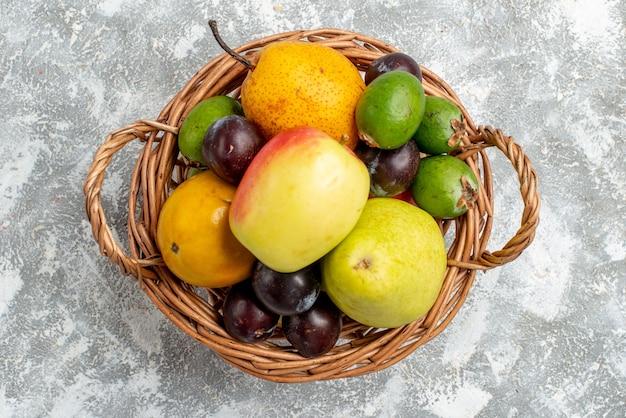 Widok z góry wiklinowy kosz z jabłkami, gruszkami, śliwkami feykhoas i persimmonami na szarym stole
