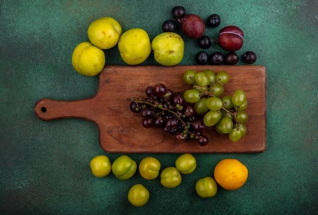 Widok z góry winogron na deskę do krojenia z wzorem śliwki, śliwki, jagody winogron i nektakot na zielonym tle