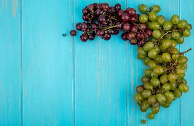 Widok z góry winogron na niebieskim tle z miejsca na kopię