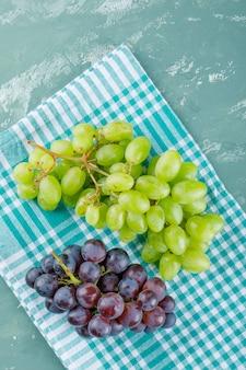 Widok z góry winogron na tle tkaniny piknikowej i tynku