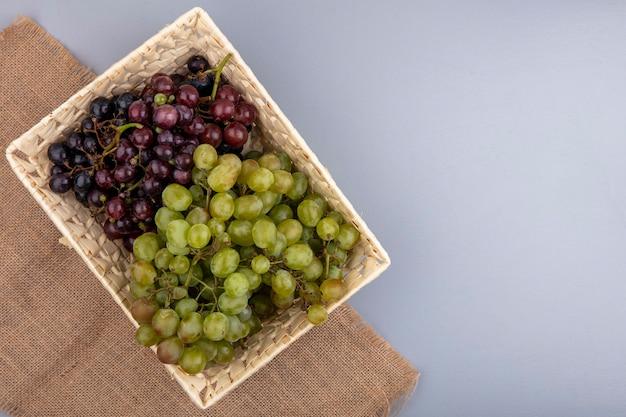Widok z góry winogron w koszu na worze na szarym tle z miejsca na kopię