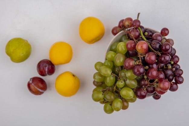 Widok z góry winogron w misce z poletkami i nektakotami na białym tle