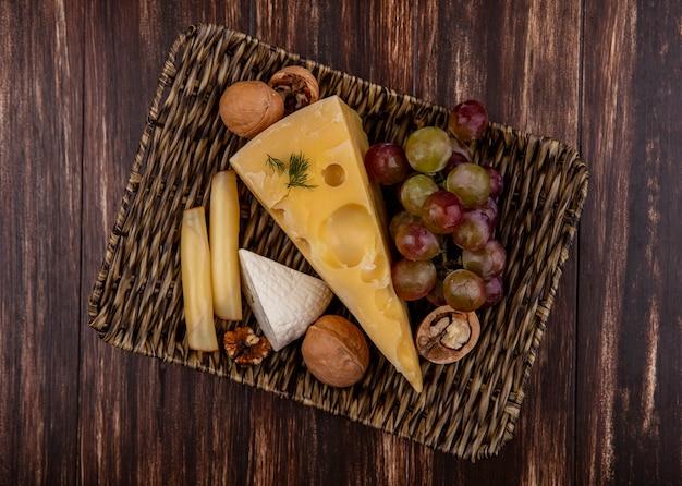 Widok z góry winogron z odmian serów i orzechów na stojaku na drewnianym tle