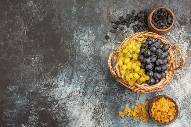 Widok z góry winogrona kosz kiści winogron między dwiema miskami suszonych owoców
