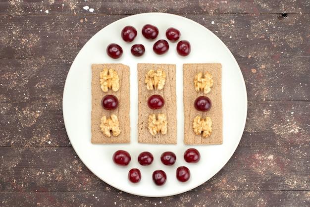 Widok z góry wiśnie i chipsy z orzechami włoskimi na białym talerzu na brązowym, owocowym krakersie