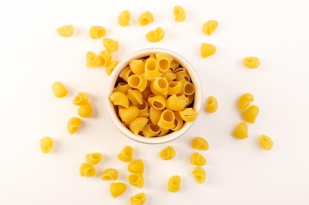 Widok z góry włoski suchy makaron surowy żółty makaron wewnątrz miski na białym tle