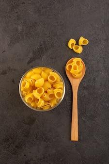 Widok z góry włoski suchy makaron żółty surowy wewnątrz miski odizolowane na łyżce w ciemności