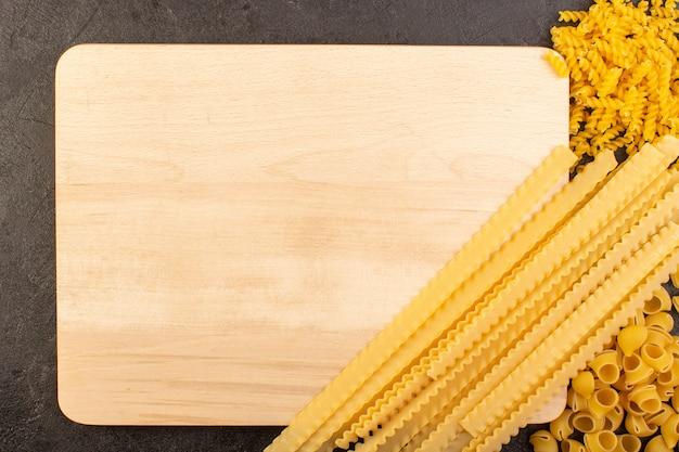 Widok z góry włoski suchy makaron żółty surowy wraz z kwadratowym utworzonym kremowym biurkiem odizolowane w ciemności