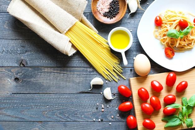 Widok z góry włoskich składników na pomidorowe i bazyliowe spaghetti.