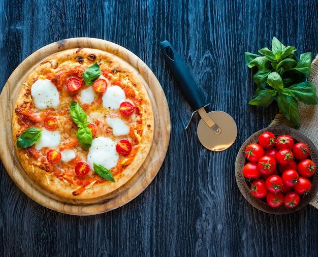 Widok z góry włoskiej klasycznej pizzy margherita nad drewnianym stołem z dodatkami