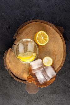 Widok z góry woda z cytryną świeży chłodny napój w szkle z kostkami lodu z pokrojonymi cytrynami na ciemnym tle koktajl napój owoc