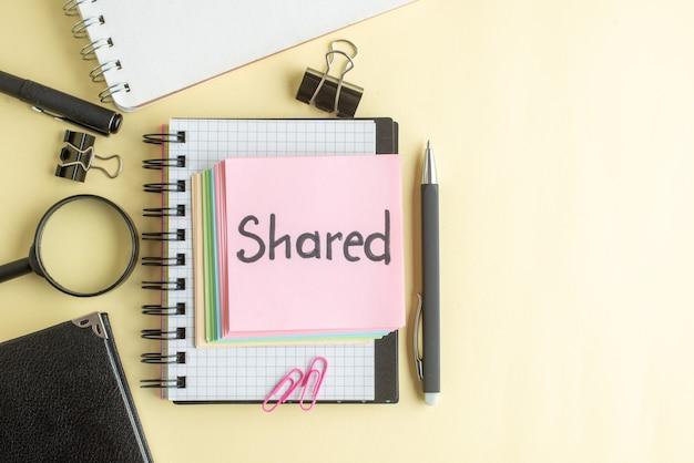 Widok z góry wspólna pisemna notatka wraz z kolorowymi niewielkimi papierowymi notatkami na jasnym tle notatnik długopis pracy biuro szkoła biznes pieniądze kolor zeszyt roboczy