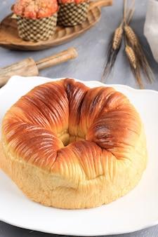 Widok z góry wybrane skupienie chleb z wełny, domowej roboty wirusowy japoński brioche hokkaido shokupan chleb mleczny z piękną teksturą jak bułka z wełny. podawany na białym talerzu, szarym tle cementu