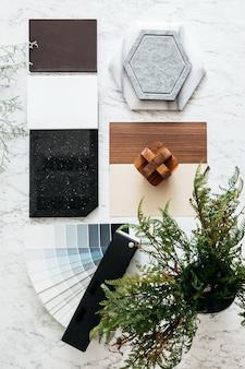Widok z góry wybranych materiałów, w tym płytki granitowej, płytki marmurowej, płytki akustycznej, laminatu z drewna orzechowego i jesionowego oraz pomalowanej próbki koloru z rośliną.