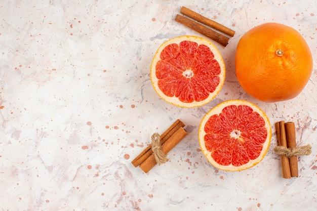 Widok z góry wycięte grejpfruty świeże grapefruitowe laski cynamonu na nagiej powierzchni wolnej przestrzeni