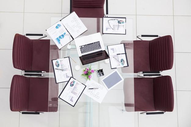 Widok z góry - wykresy finansowe, marketingowe, zeszyty i długopisy na stanowisku pracy w pustym biurze.