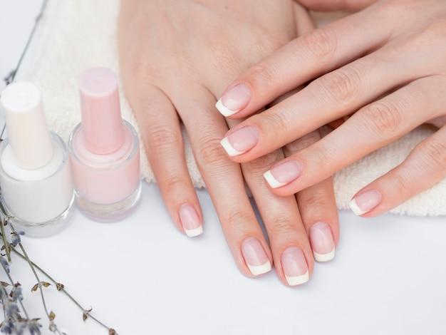 Widok z góry wypielęgnowane dłonie i lakier do paznokci