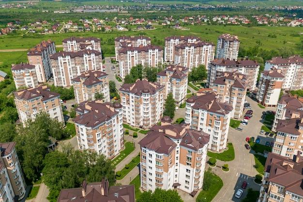 Widok z góry wysokich budynków mieszkalnych lub biurowych, zaparkowanych samochodów, krajobrazu miejskiego miasta.