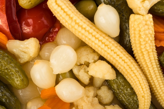 Widok z góry wzór mieszanych marynat. marynowany ogórek, marchewka, cebula perlowa, kukurydza, papryka czerwona, kalafior, oliwki i kapary