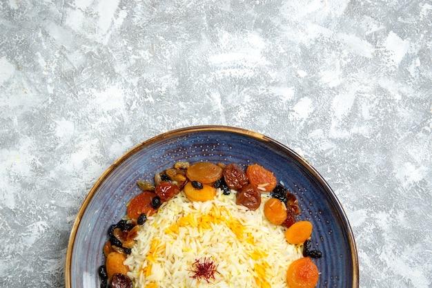 Widok z góry yummy shakh plov gotowany ryż z rodzynkami wewnątrz płyty na jasnobiałym tle