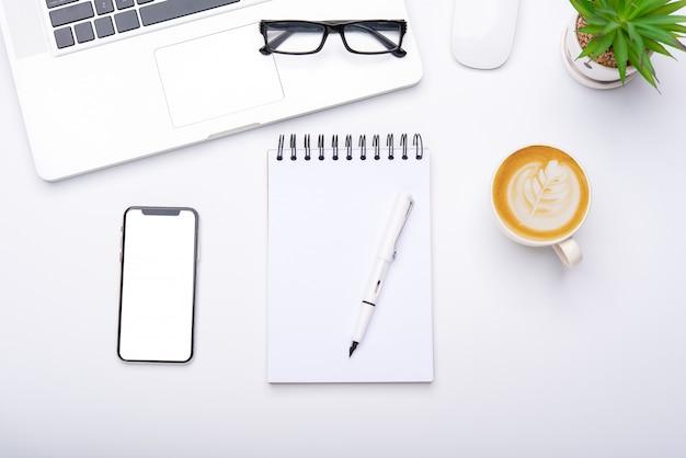 Widok z góry z biurkiem z laptopem, telefonem komórkowym, ołówkową filiżanką i okularami w biurze.