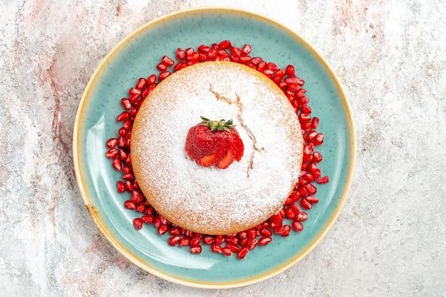 Widok z góry z bliska apetyczne ciasto apetyczne ciasto z truskawkami i pestkami granatów na niebieskim talerzu