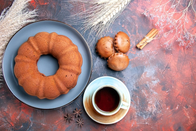 Widok z góry z bliska apetyczne ciasto ciasto babeczki filiżanka herbaty cynamonowe pszenne kłosy