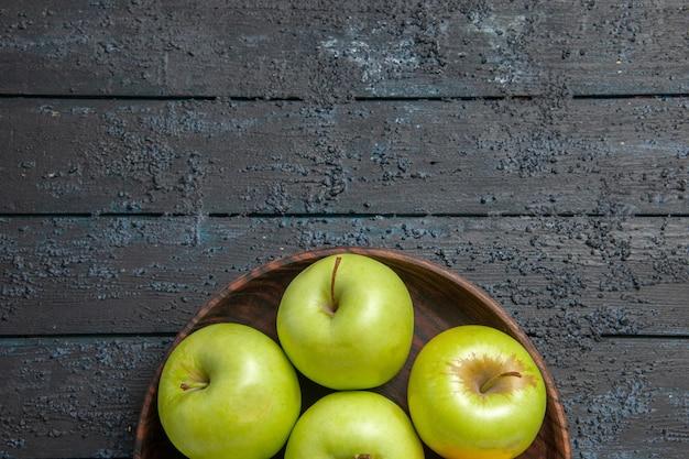 Widok z góry z bliska apetyczne jabłka siedem zielono-żółtych jabłek na talerzu na ciemnej powierzchni