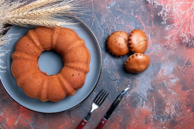 Widok z góry z bliska babeczki pszenne uszy gałęzie obok ciasta babeczki widelec i nóż