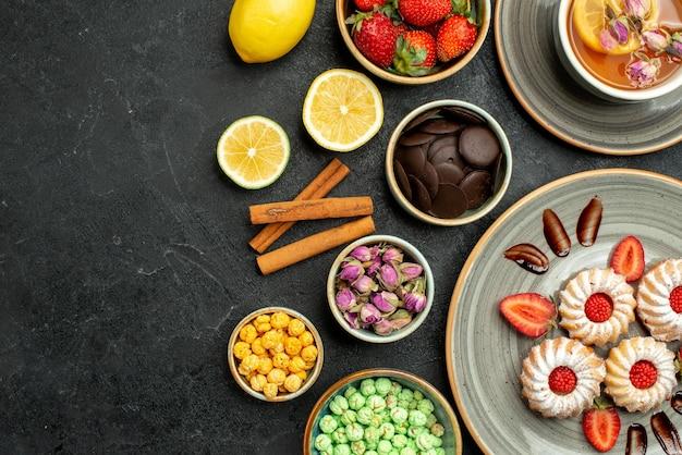 Widok z góry z bliska ciasteczka z herbatnymi ciasteczkami z truskawkową czarną herbatą z cytrynowymi miseczkami czekolady i różnymi słodyczami po prawej stronie stołu