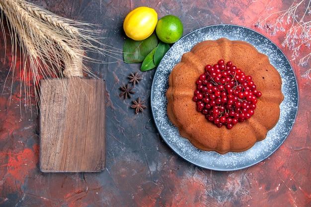 Widok z góry z bliska ciasto cytryny limonki liście anyż gwiazdkowaty z deską do krojenia czerwonych porzeczek