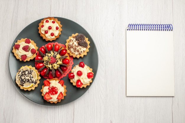 Widok z góry z bliska ciasto czekoladowe zaokrąglone z tarty jagodowe w szarym talerzu i notatnik na białym drewnianym stole