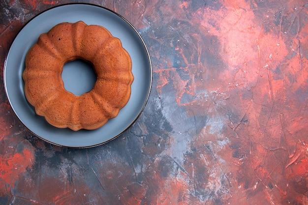 Widok z góry z bliska ciasto niebieski talerz apetycznego ciasta na niebiesko-czerwonym stole