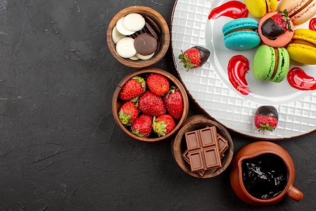 Widok z góry z bliska czekolada cztery miski czekoladowych truskawek i kremu czekoladowego obok talerza francuskich makaroników i truskawek na stole