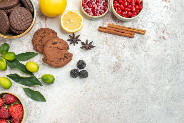 Widok z góry z bliska czekoladowe ciasteczka laski cynamonu czekoladowe ciasteczka miski jagód owoce cytrusowe na stole