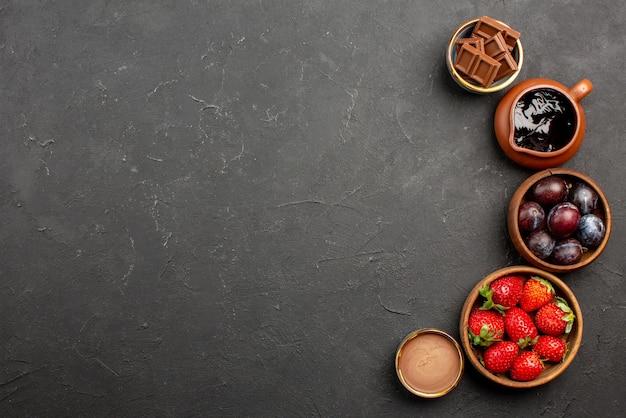 Widok z góry z bliska czekoladowe jagody brązowe miski z truskawkami sos czekoladowy i jagody po prawej stronie ciemnego stołu