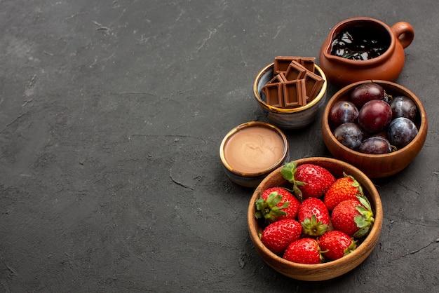 Widok z góry z bliska czekoladowe jagody drewniane miski truskawek czekoladowe jagody i sos czekoladowy po prawej stronie ciemnego stołu