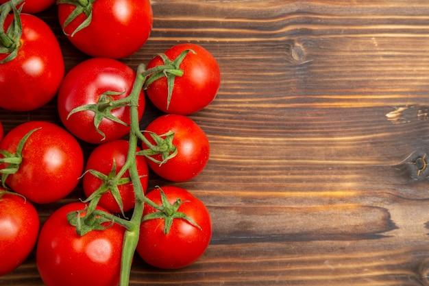 Widok z góry z bliska czerwone pomidory dojrzałe warzywa na brązowym drewnianym biurku czerwona sałatka dojrzała świeża dieta
