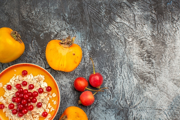Widok z góry z bliska czerwone porzeczki apetyczny persimmons czerwone porzeczki w wiśni miska