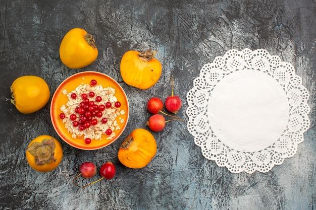 Widok z góry z bliska czerwone porzeczki trzy persimmons czerwone porzeczki w serwetce koronki miska wiśni