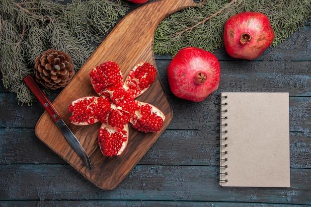 Widok z góry z bliska czerwony granat na desce zgnieciony granat na desce do krojenia obok dojrzałych trzech granatów nóż biały notatnik i świerkowe gałązki i szyszki na stole