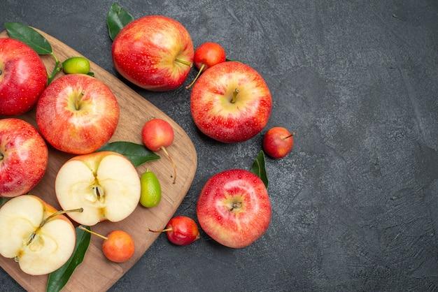 Widok z góry z bliska jabłka jabłka z liśćmi deska z owocami cytrusowymi, wiśniami i jabłkami