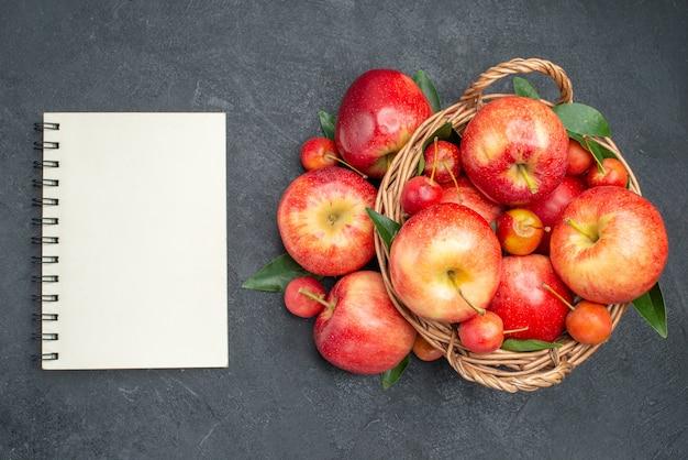 Widok z góry z bliska jabłka liny jabłka wiśnie w koszyku notebooka