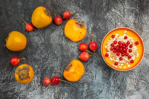 Widok z góry z bliska jagody apetyczne persymony wiśniowe obok miski czerwonych porzeczek