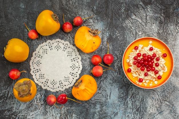 Widok z góry z bliska jagody apetyczny persimmons wiśniowy wokół koronki serwetka miska czerwonych porzeczek