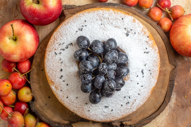 Widok z góry z bliska jagody, jabłka i jagody wokół ciasta z winogronami na drewnianej desce